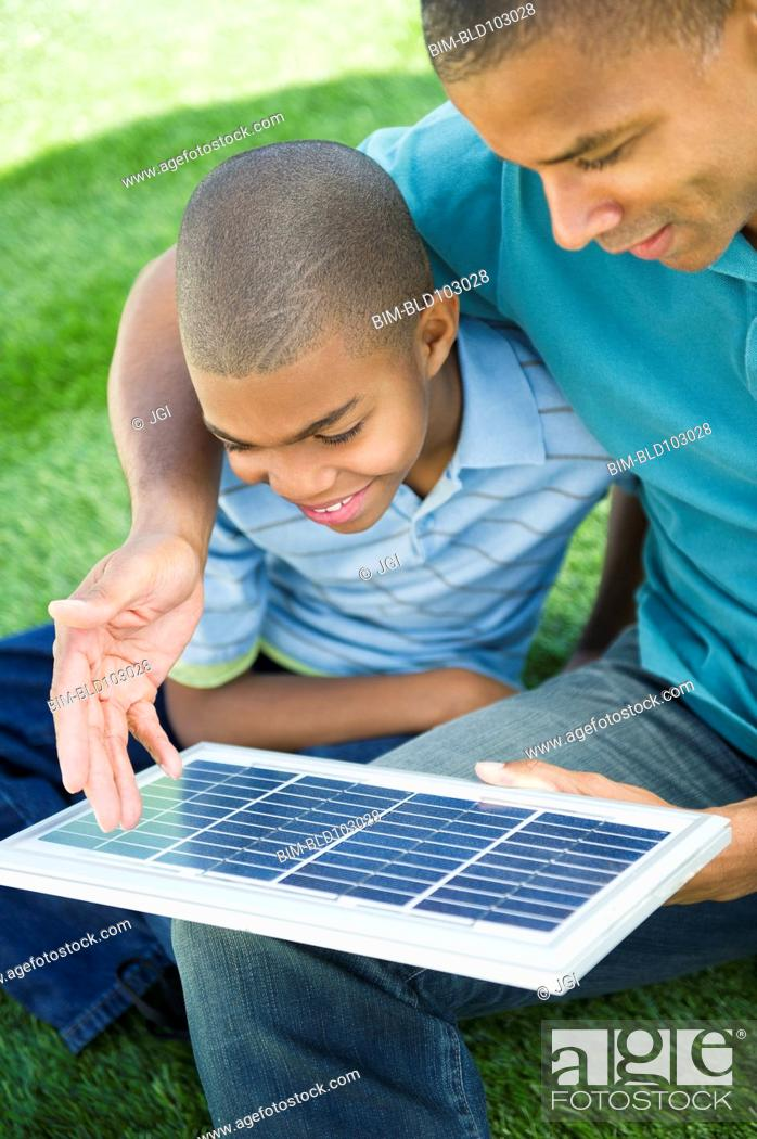 Imagen: Father and son looking at solar panel.