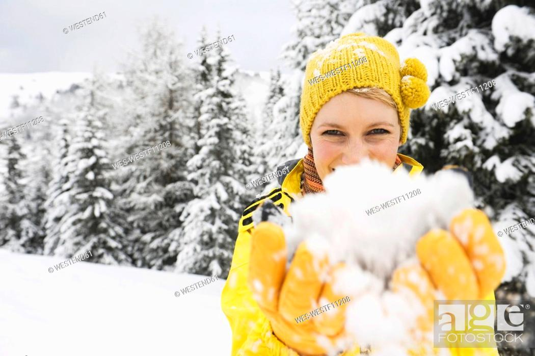 Stock Photo: Italy, South Tyrol, Young woman fooling about with snow, portrait.