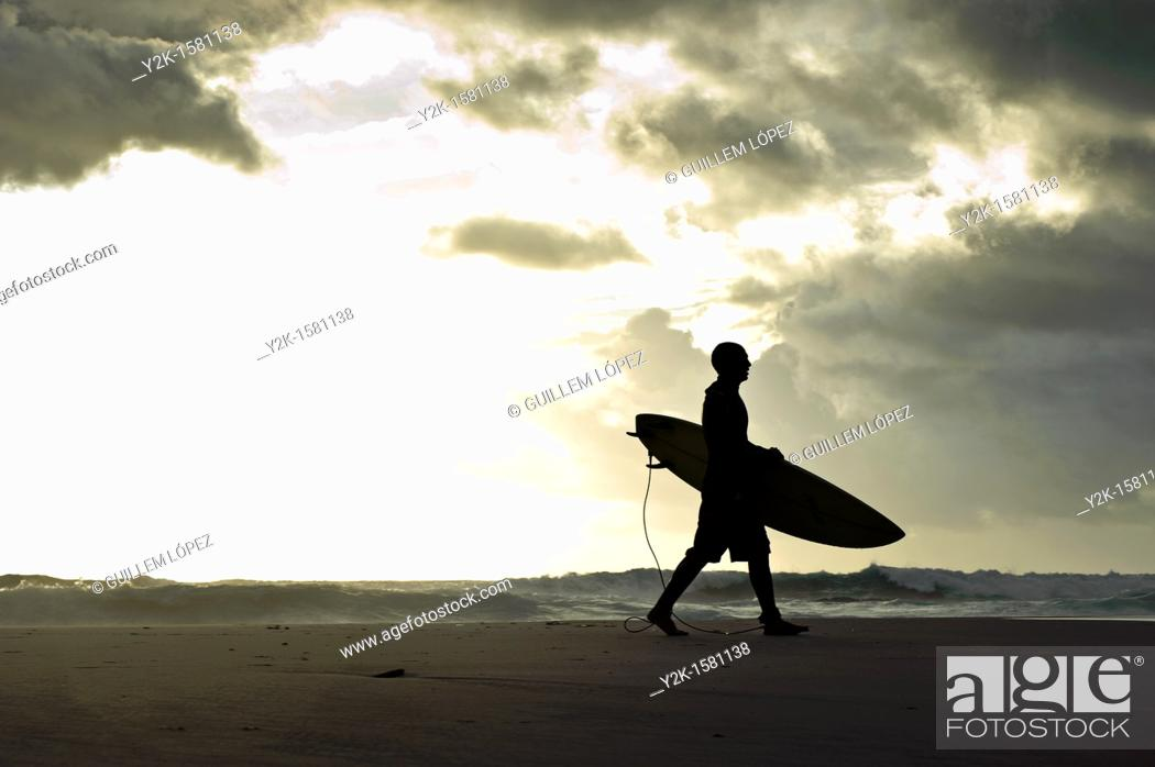 Stock Photo: Silhouette of a surfer walking with his surfboard along the beach with stormy clouds in the background, Tarifa, Andalucia, Spain.