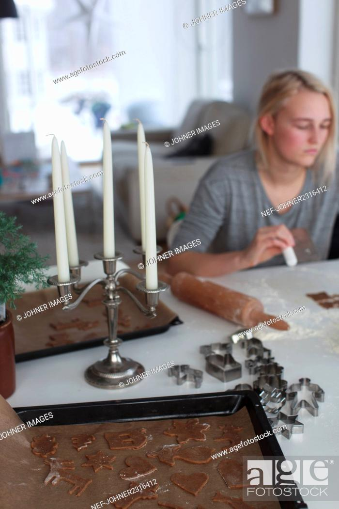 Stock Photo: Young woman preparing gingerbread cookies.