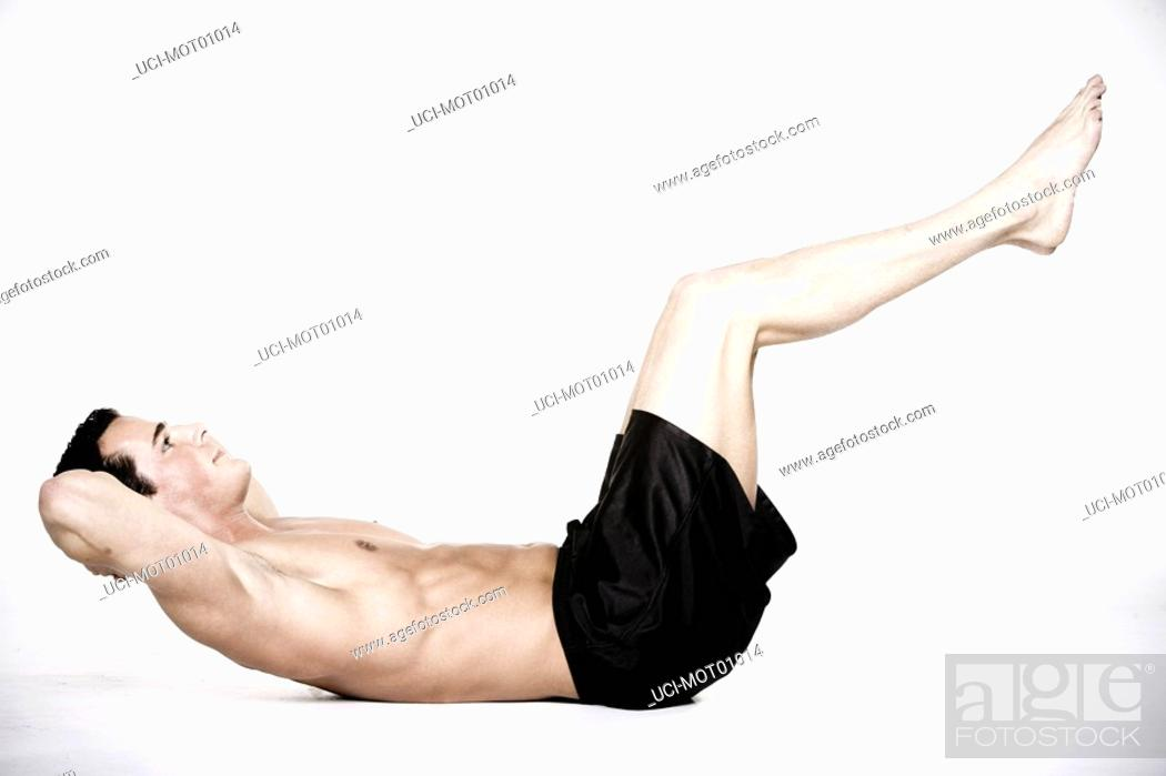 Stock Photo: Bare-chested man doing sit-ups.