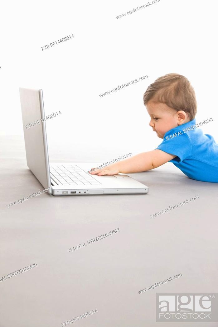 Stock Photo: Baby on floor with laptop.