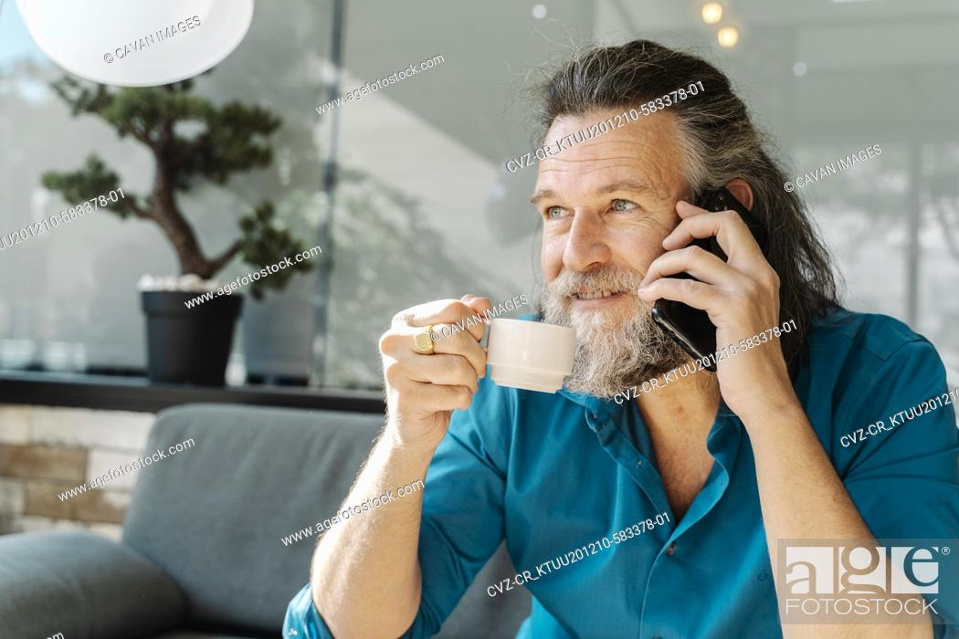 Stock Photo: Mature man with beard talking on the phone and drinking coffee sitting.