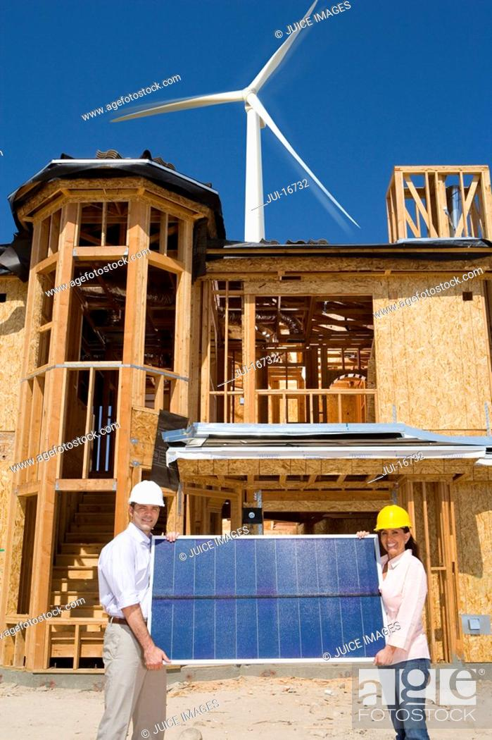 Stock Photo: Couple holding solar panel on construction site.