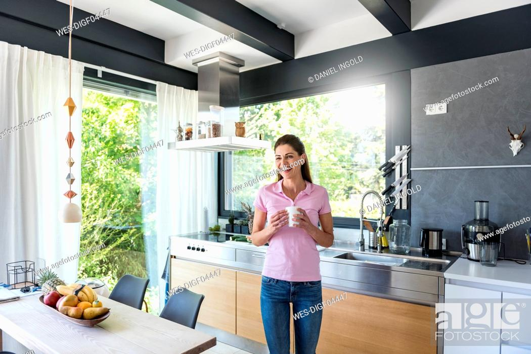 Stock Photo: Laughing woman at home in kitchen with cup of coffee.