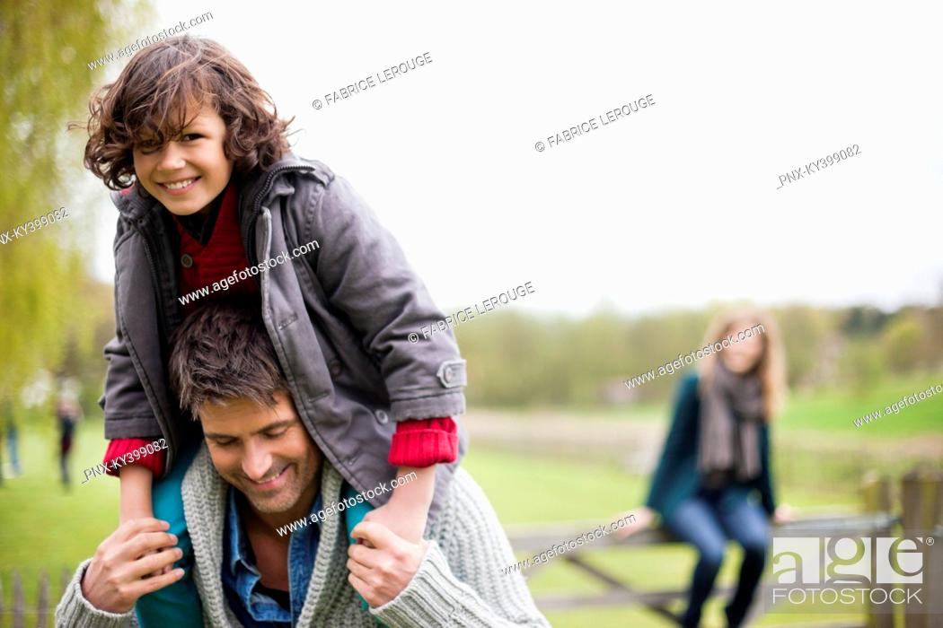 Stock Photo: Man carrying his son on shoulders.