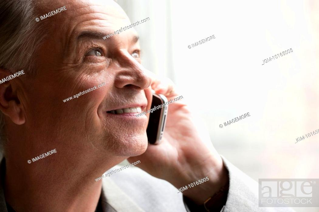 Stock Photo: Senior businessman holding mobile phone and looking up with smile.