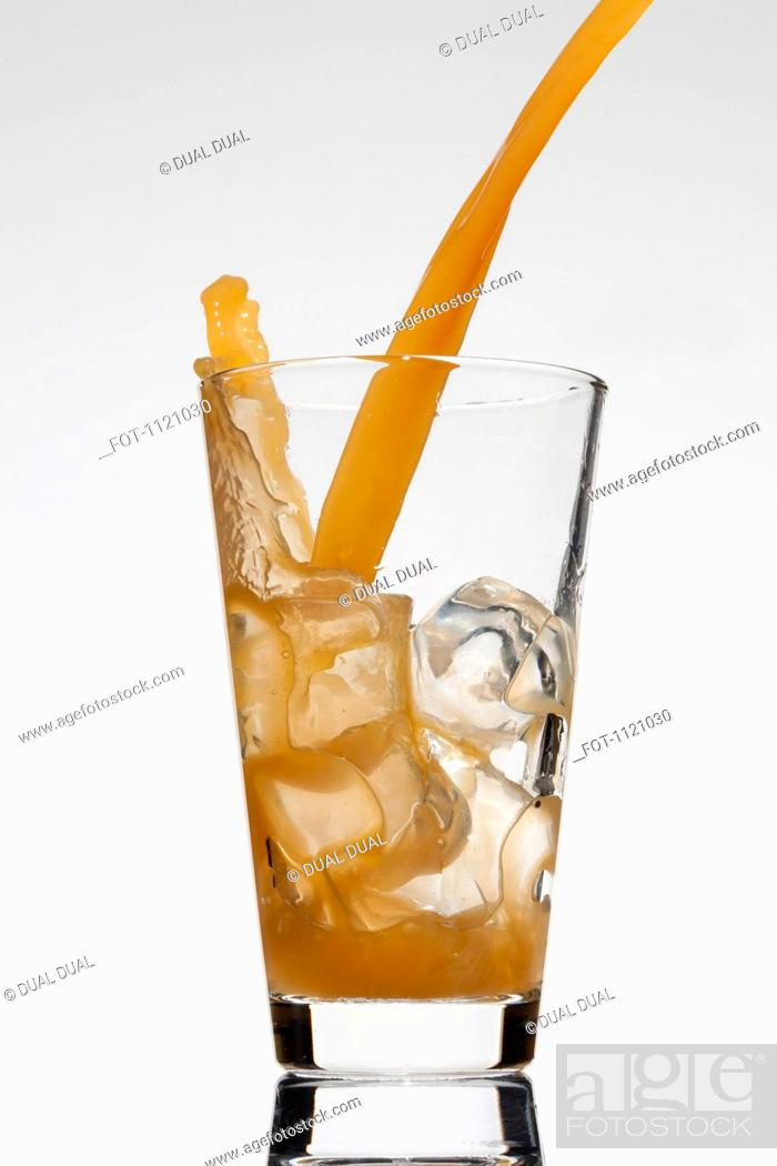 Stock Photo: A drink being poured into a glass.
