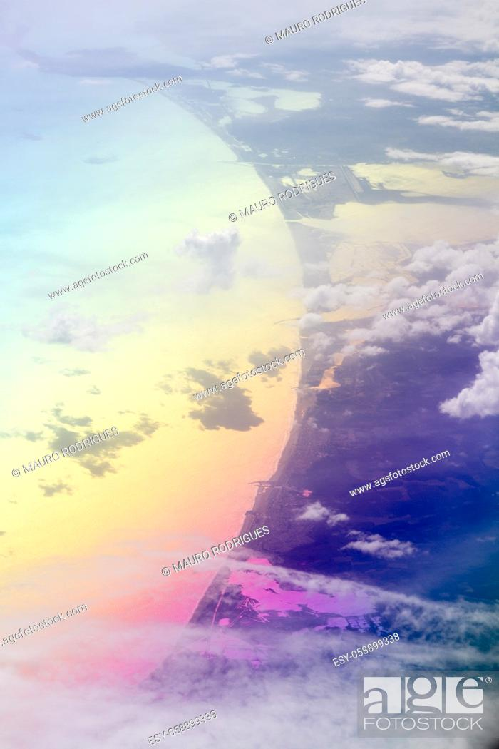 Stock Photo: Aerial view of lake and white clouds seen from a plane.