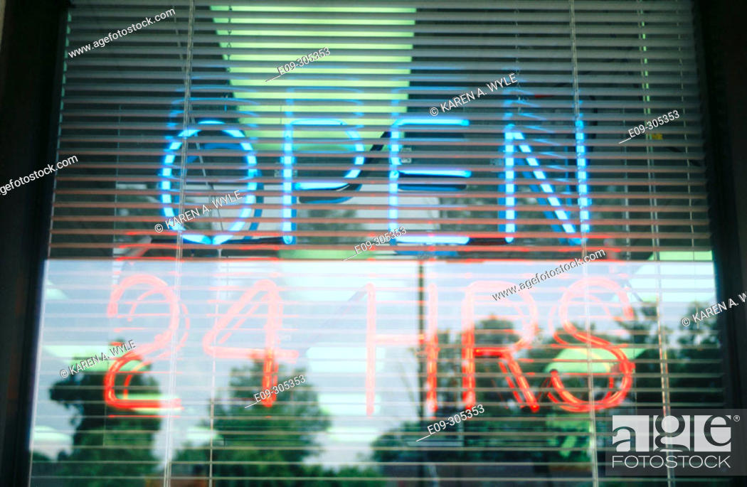 Stock Photo: neon 'Open 24 Hrs' sign in window, blue and orange, Indiana, USA.