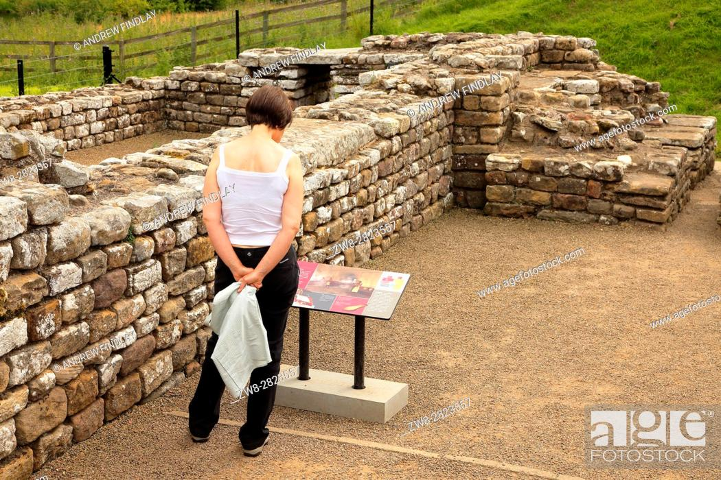 Stock Photo: Woman reading information sign. Chesters Roman Fort and Museum bathhouse. Chollerford, Hexham, Northumberland, England, United Kingdom, Europe.