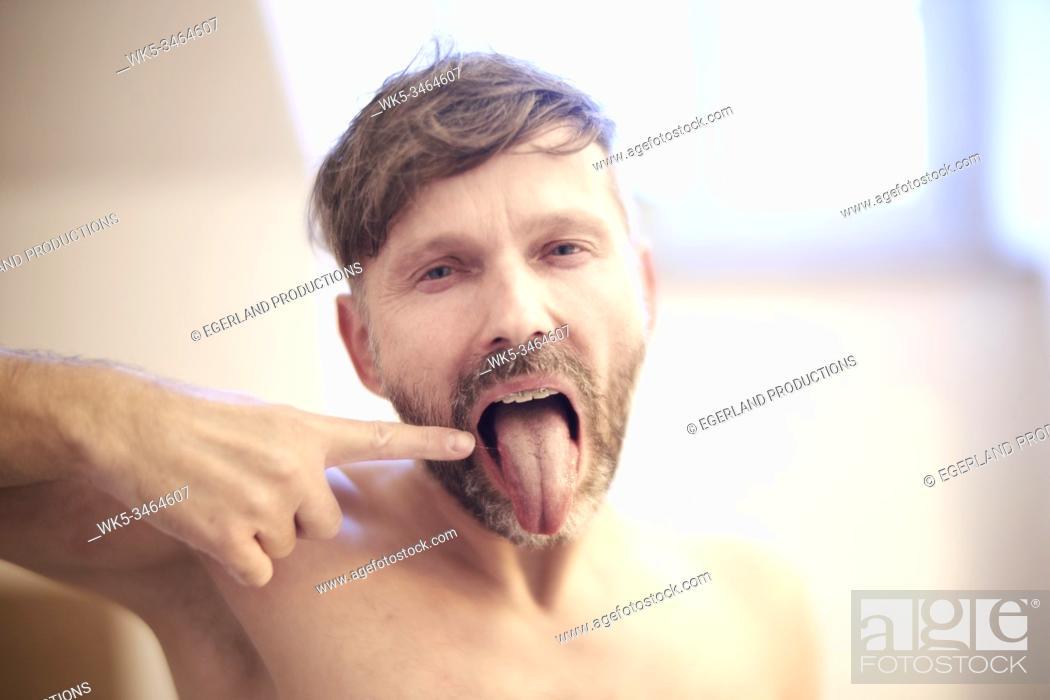 Imagen: Sleepy man looking at his tongue.