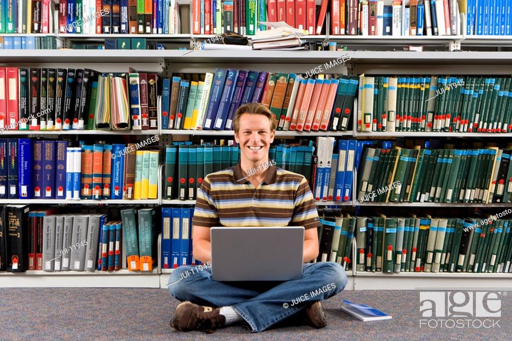 Stock Photo: Young man studying in library, on floor with laptop computer and legs crossed, smiling, portrait.