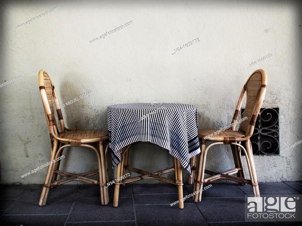 Imagen: Two wicker chairs with a table and tablecloth on the terrace of a bar.