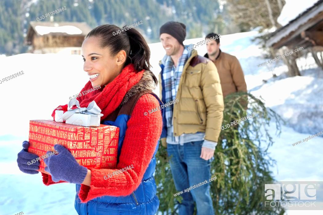 Stock Photo: Smiling friends with fresh cut Christmas tree and gifts in snow.
