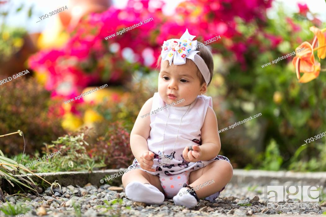 Imagen: little girl sitting in the garden playing with rocks.