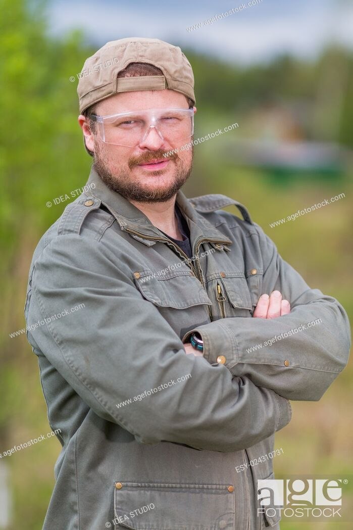 Stock Photo: Solid worker in safety glasses on natural background.