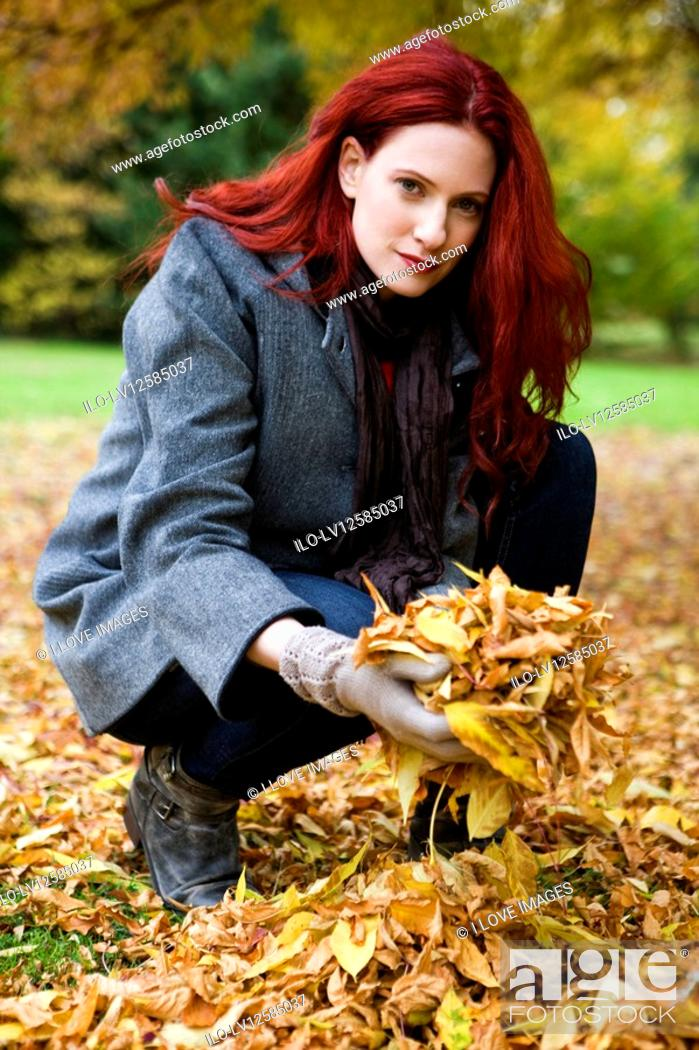 Stock Photo: A young woman holding a handful of autumn leaves.