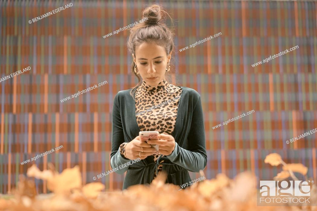 Stock Photo: fashionable woman using smart phone, typing text message, in front of geometrical pattern, lines, autumn season, in Munich, Germany.