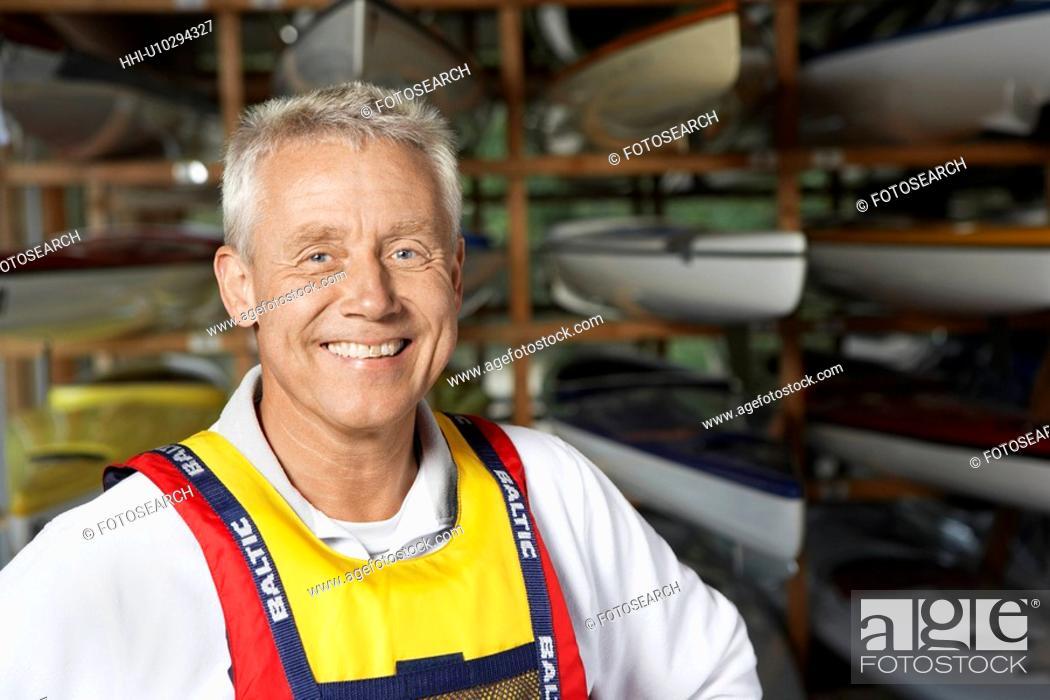 Stock Photo: Mature man by kayaks.