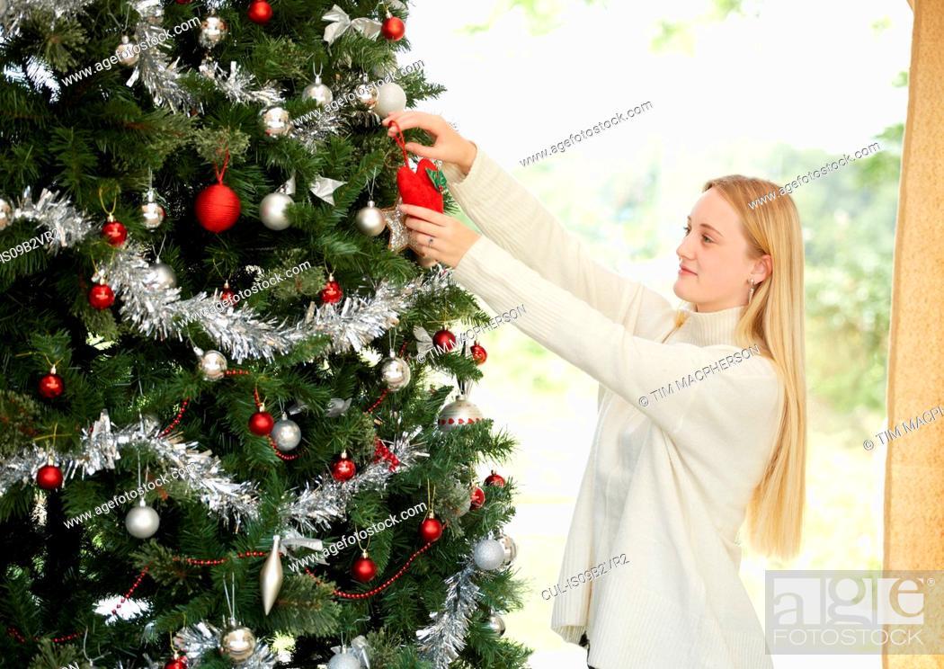 Stock Photo: Teenage girl hanging decorations on christmas tree.