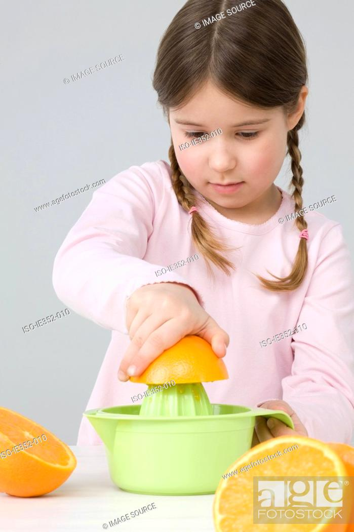 Stock Photo: Girl juicing oranges.