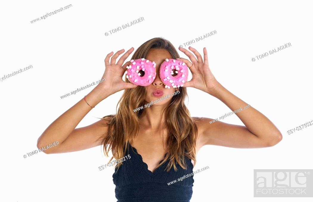 Imagen: Teen girl holding donuts on her eyes as goggles at white background.