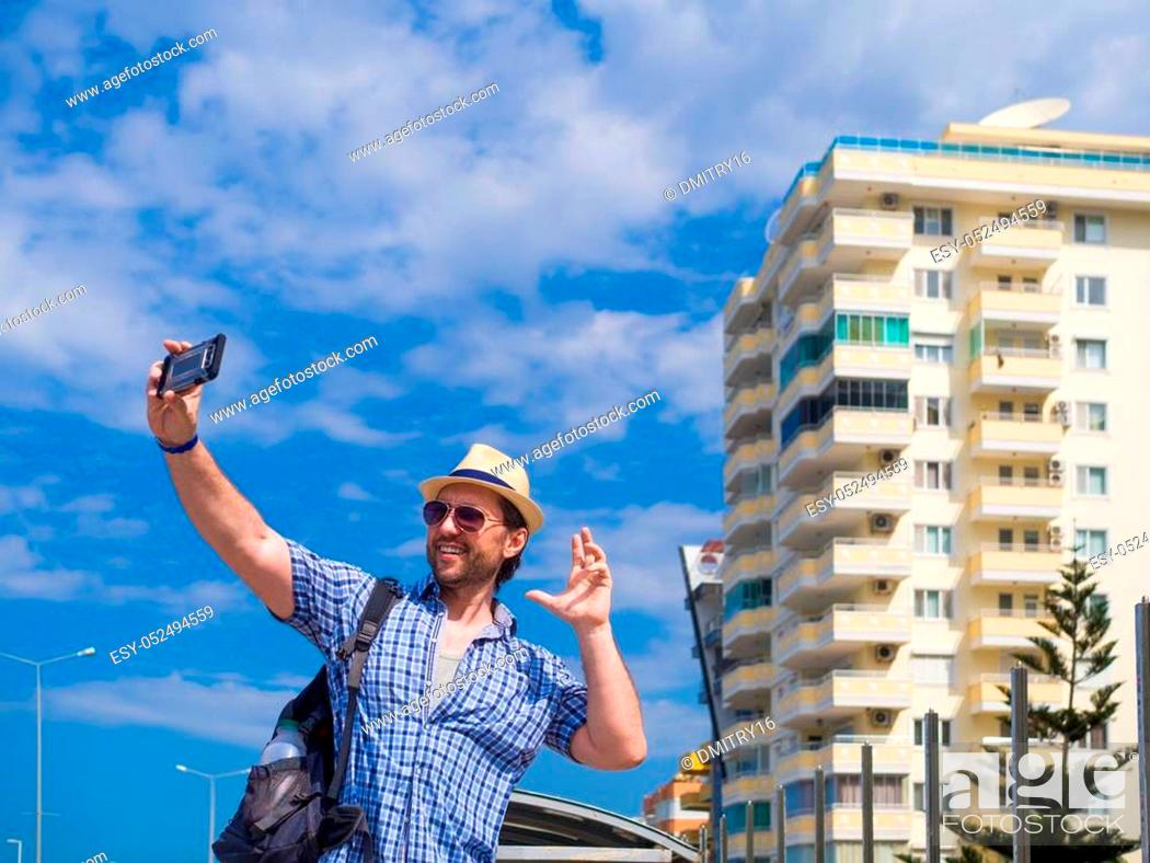 Stock Photo: Delighted young man in trendy checkered shirt spending time outdoor, exploring the surroundings in morning. Smiling guy in hat and sunglasses having fun.