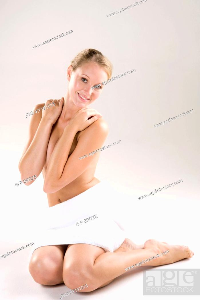Stock Photo: Portrait of a woman covering her breast and smiling.