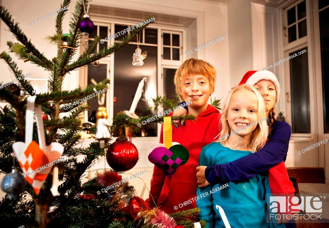 Stock Photo: Children smiling with Christmas tree.