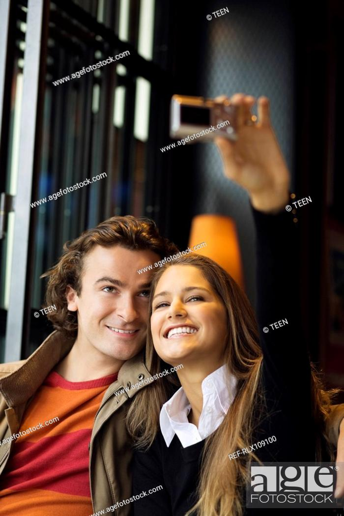 Stock Photo: Young couple in street cafe, taking photo, Paris, France.