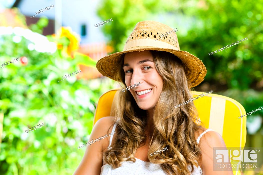 Photo de stock: Woman tanning herself in the sun on a lounge chair and enjoying the free time in her garden.