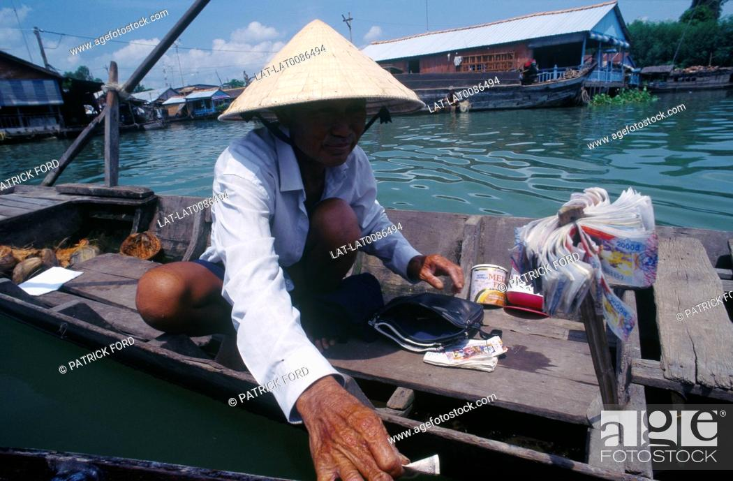 Stock Photo: Mekong delta. Man in shallow boat. Lottery tickets for sale. Bundles of currency, banknotes. Houseboat. DwellingsGames, board games.