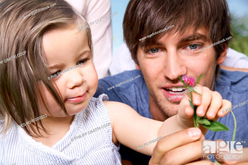 Stock Photo: Germany, Cologne, Girl holding flower with parents, close up.