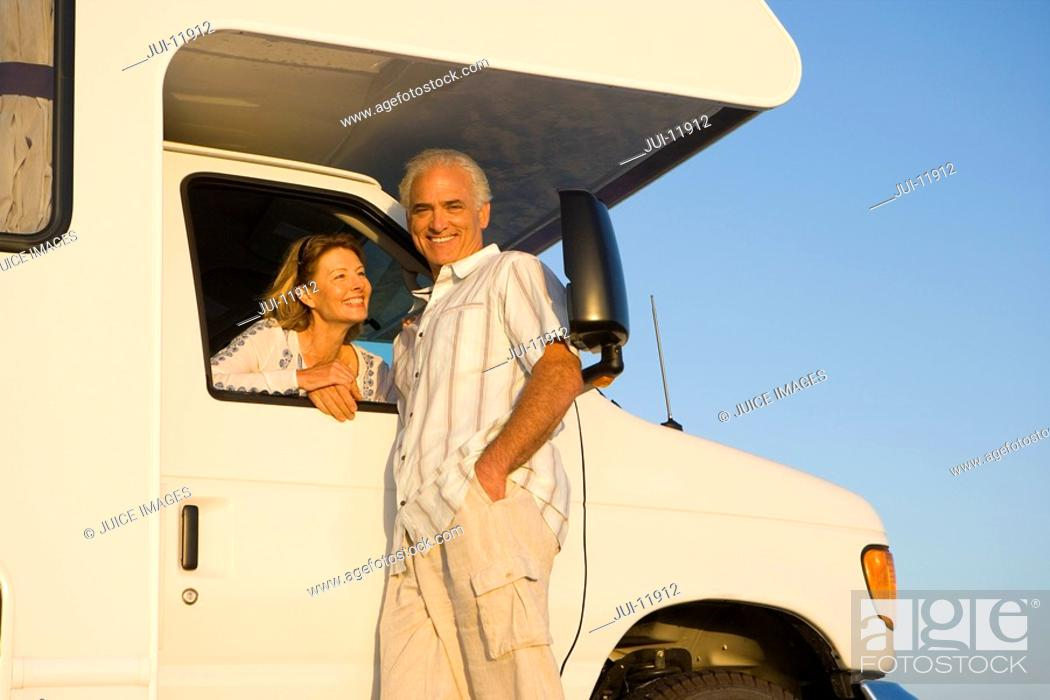 Stock Photo: Mature woman looking out window of motor home at husband, portrait of man, low angle view.