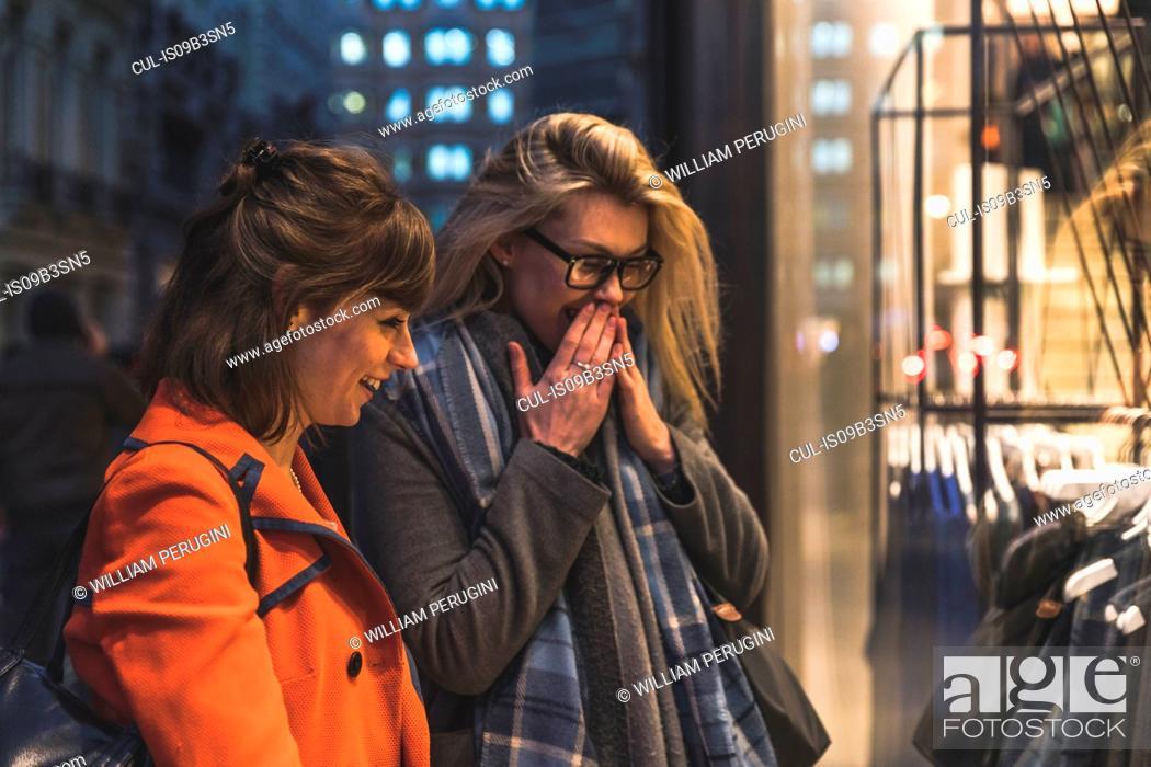 Stock Photo: Two female friends looking in shop window.