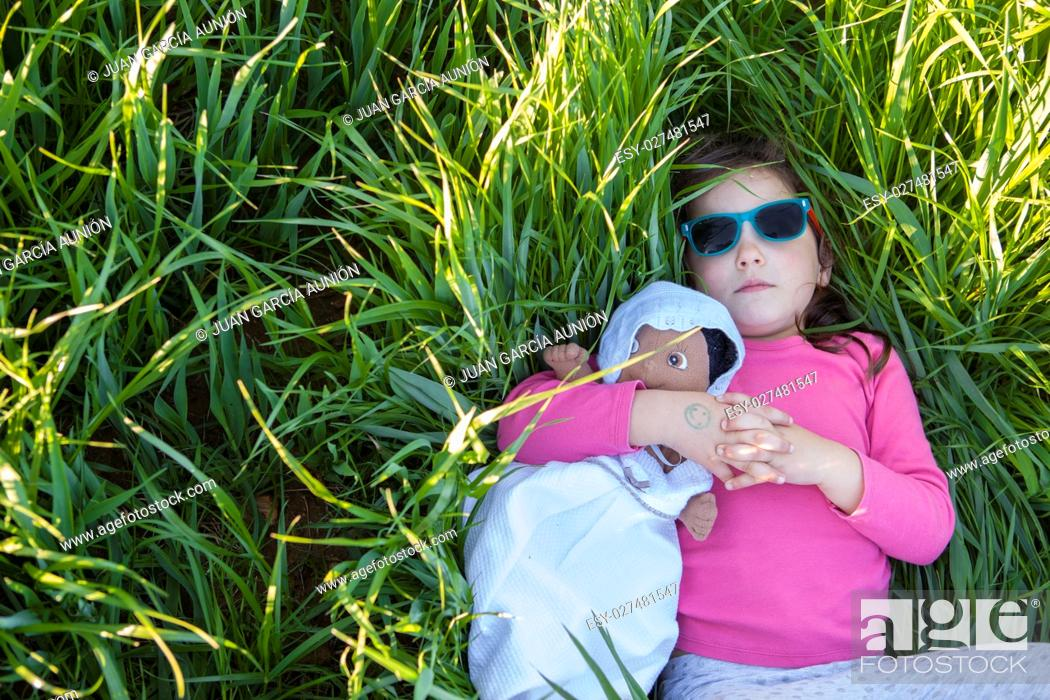 Imagen: Little girl and her doll lying on green cereal field at sunset, Spain.