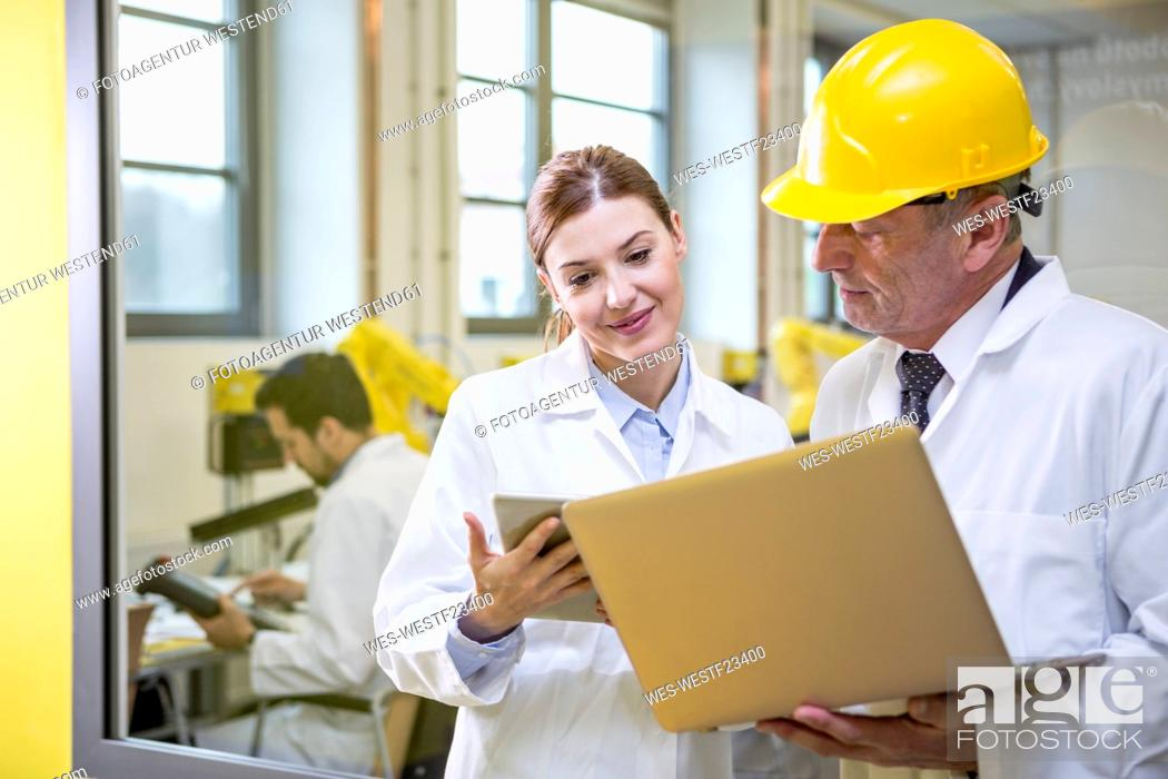 Stock Photo: Two engineers in factory with tablet and laptop.