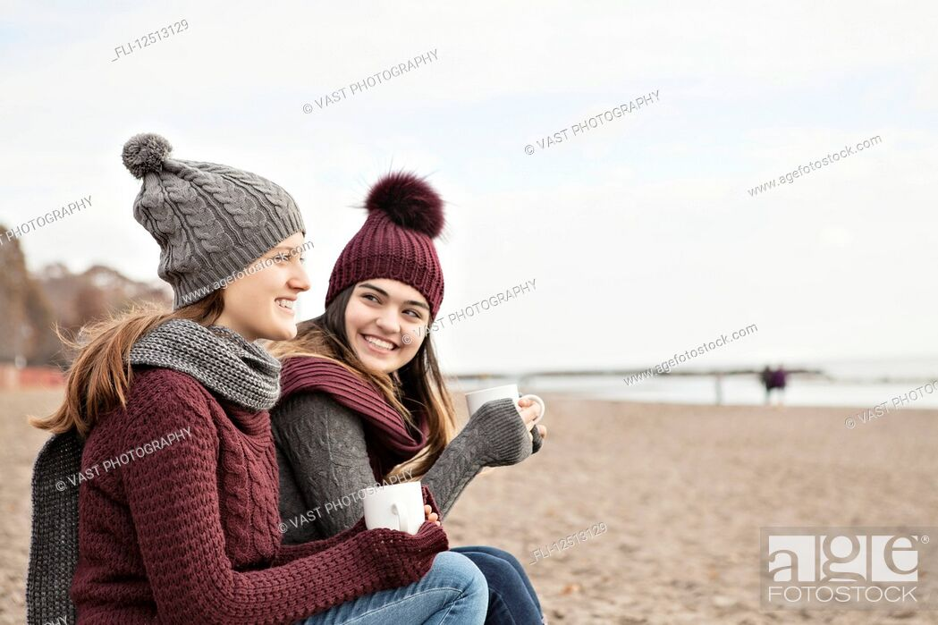 Stock Photo: Two friends at the beach wearing knit hats and scarves, sitting and having coffee together, Woodbine Beach; Toronto, Ontario, Canada.