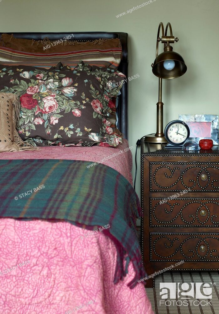 Stock Photo: Brass lamp on chest of drawers in traditional style bedroom, USA.