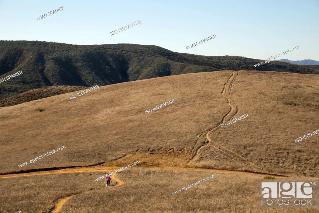Imagen: Distant view of female runner running through landscape, Thousand Oaks, California, USA.