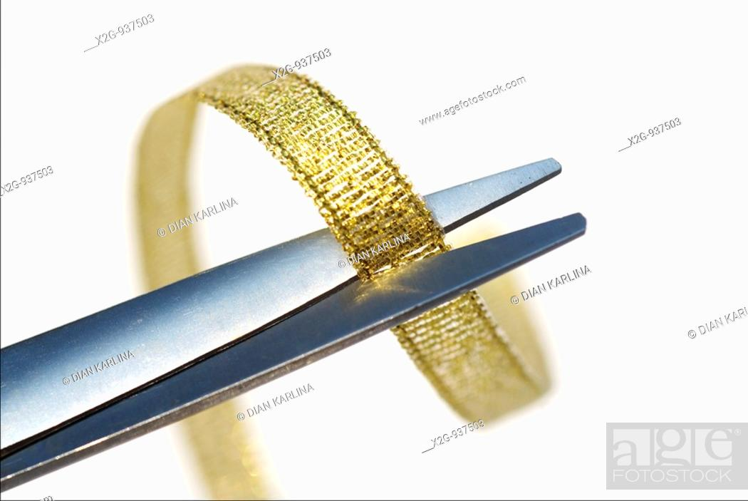 Stock Photo: Close-up of a gold ribbon and scissor.