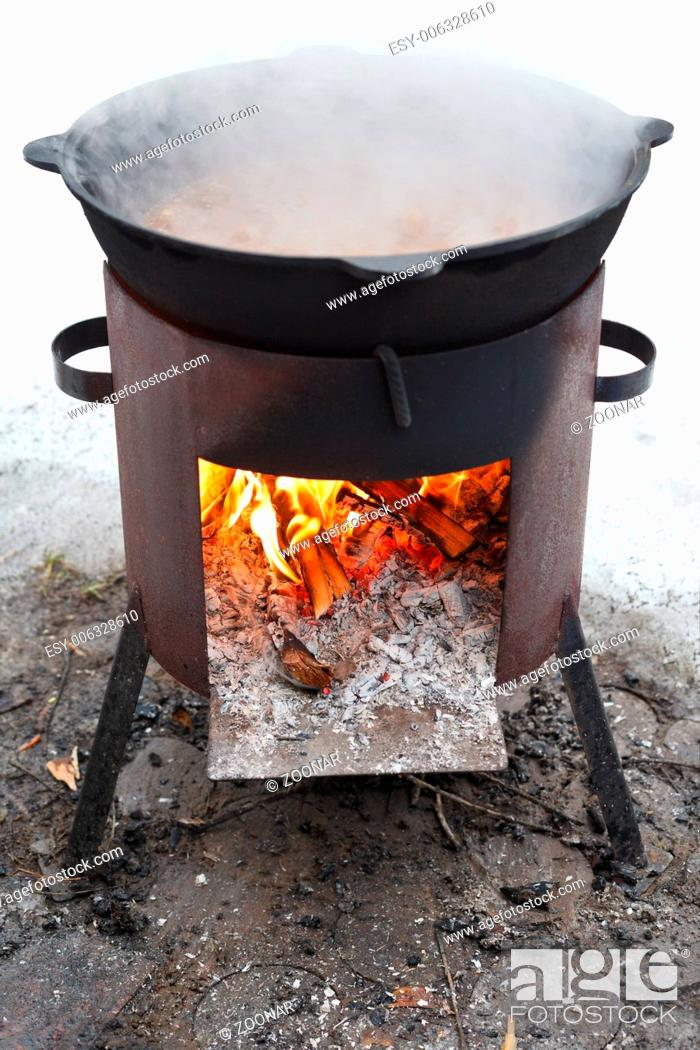 Stock Photo: cooking stew on outdoor mobile brazier.