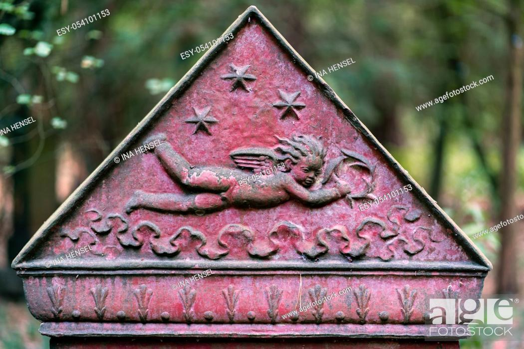 Stock Photo: Triangular part of a tombstone showing a flying cherub on red background with stars in the sky at Suedwestfriedhof cemetery, Stahnsdorf, Germany.