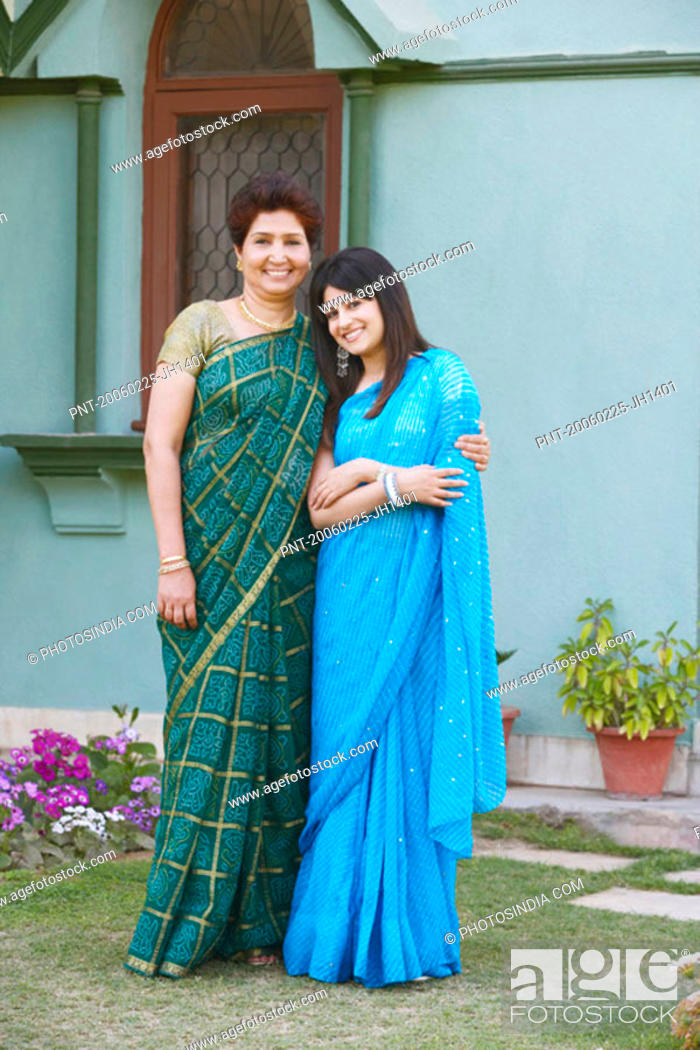 Stock Photo: Portrait of a mother with her arm around her daughter.