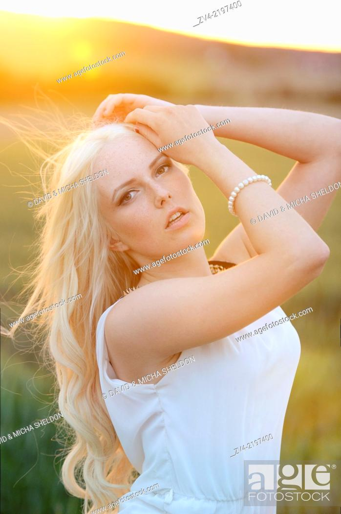 Stock Photo: Portrait of a young woman in cornfield at sunset.