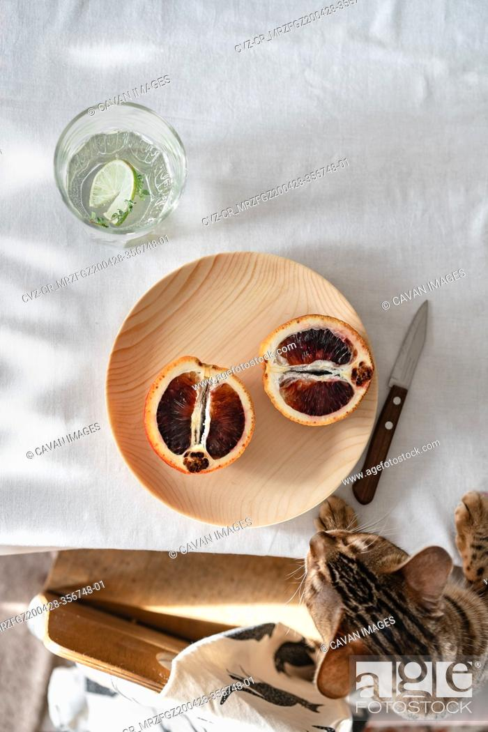 Stock Photo: Two halves of red orange on a wooden plate.