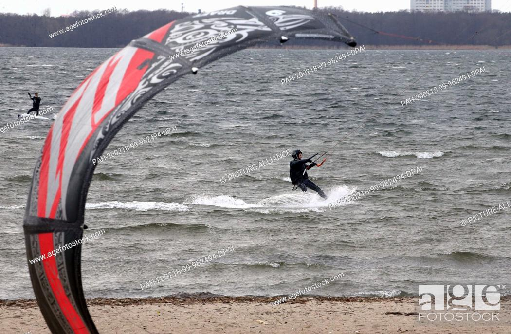 Stock Photo: 18 February 2020, Berlin: At wind speeds of up to 59 km/h and temperatures of around seven degrees Celsius, kitesurfers move across the churning water of Lake.