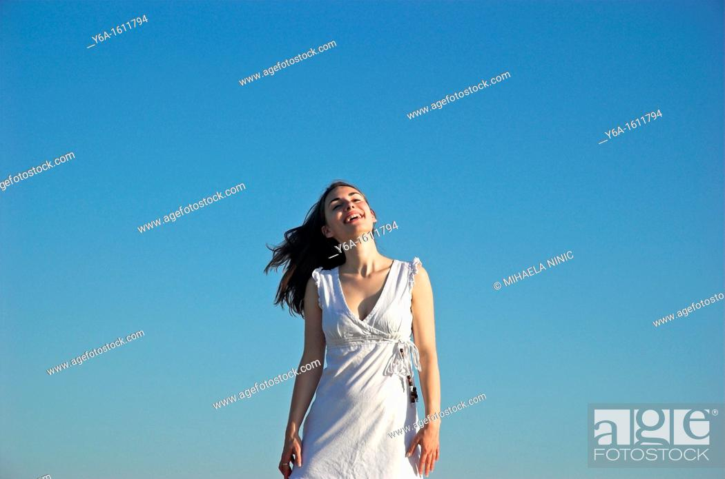 Stock Photo: Portrait of a smiling young woman wearing summer dress against blue sky.