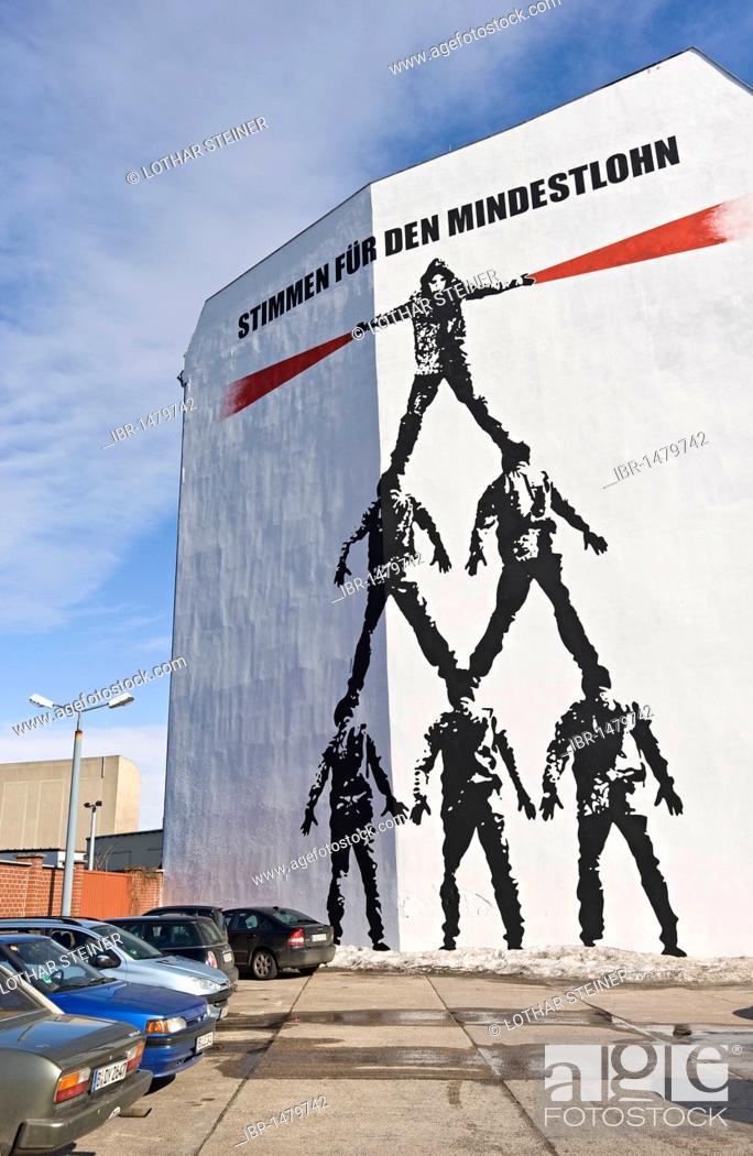 Imagen: Stimmen fuer den Mindestlohn, voices for the minimum wage, Die Menschenpyramide, man pyramid, mural by Victor Ash on Schiffbauerdamm, Berlin, Germany, Europe.